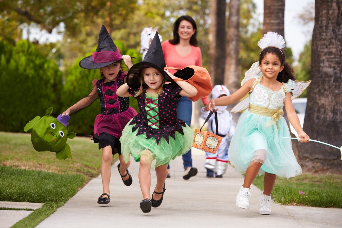 three kids trick or treating with mom behind them on sidewalk